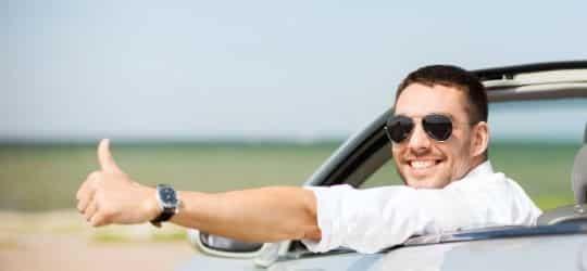 homem fazendo positivo para foto de dentro do veiculo